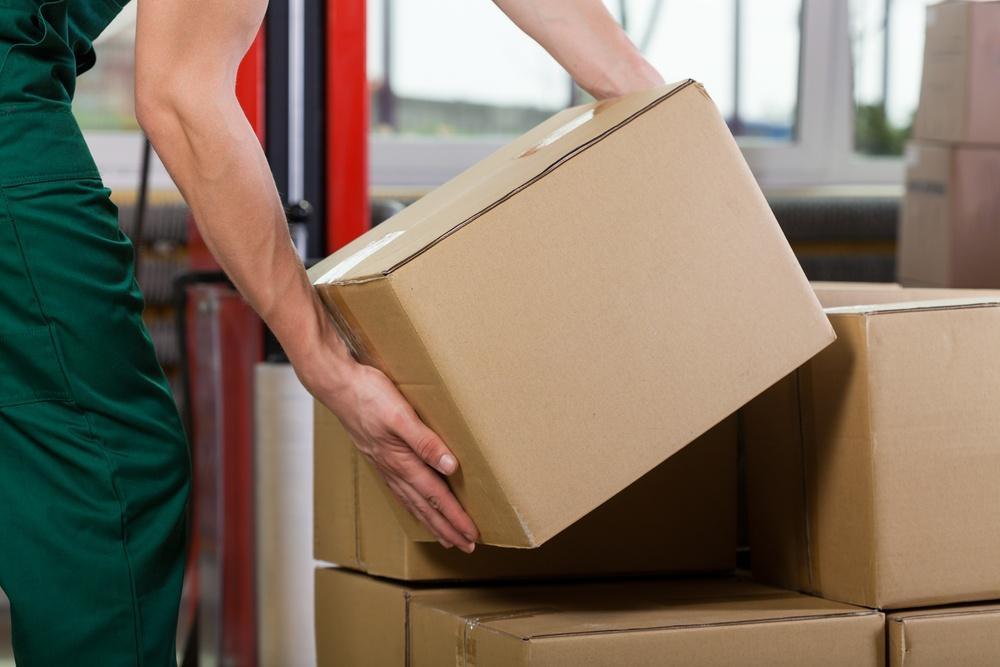Hands of warehouse worker lifting box, horizontal.jpeg